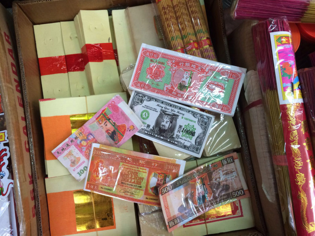 Different designs of paper money at the small Sheung Wan store. Below the banknotes are bundles of blank paper money.