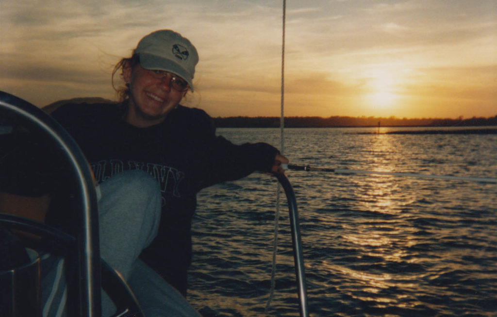 Young woman relaxing on a sailboat at sunset