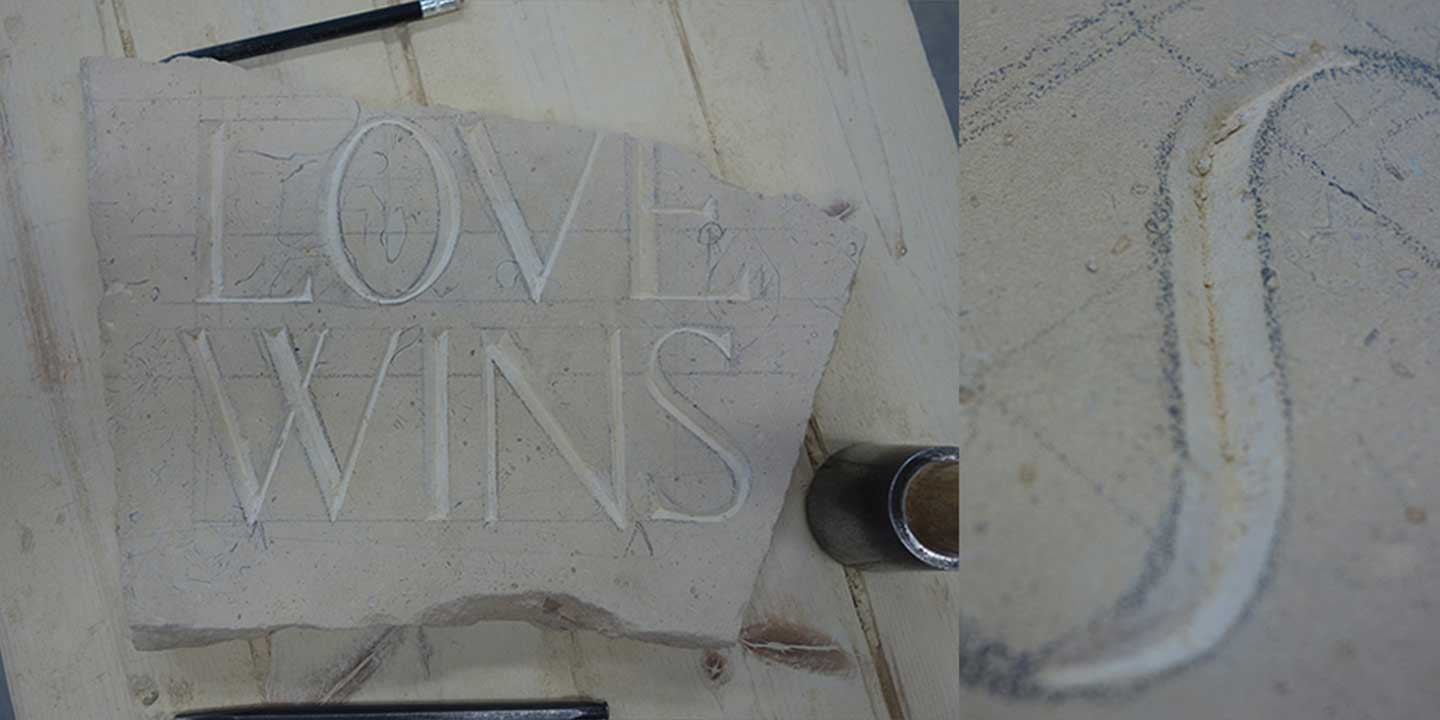 Close up image of stone carving in process with focus on curved letter s