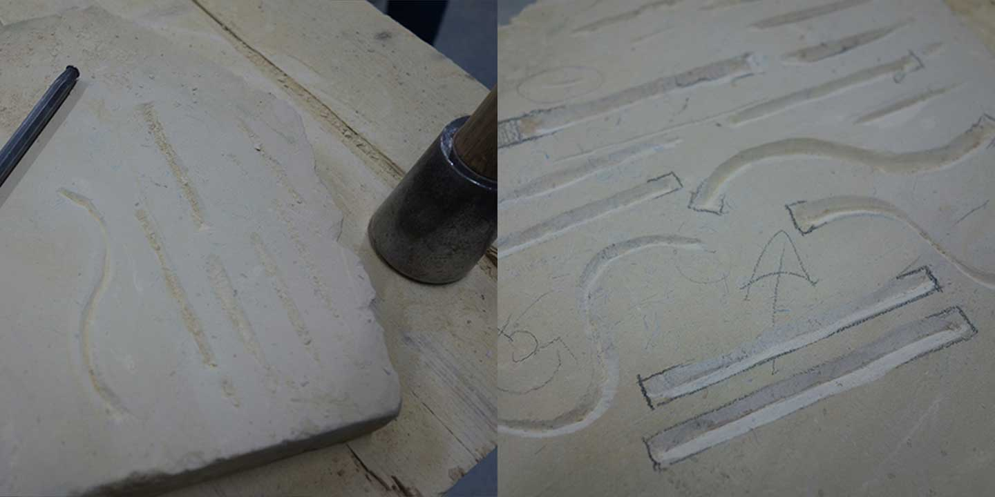 Close up image of first attempt at carving straight lines and s-curves into stone