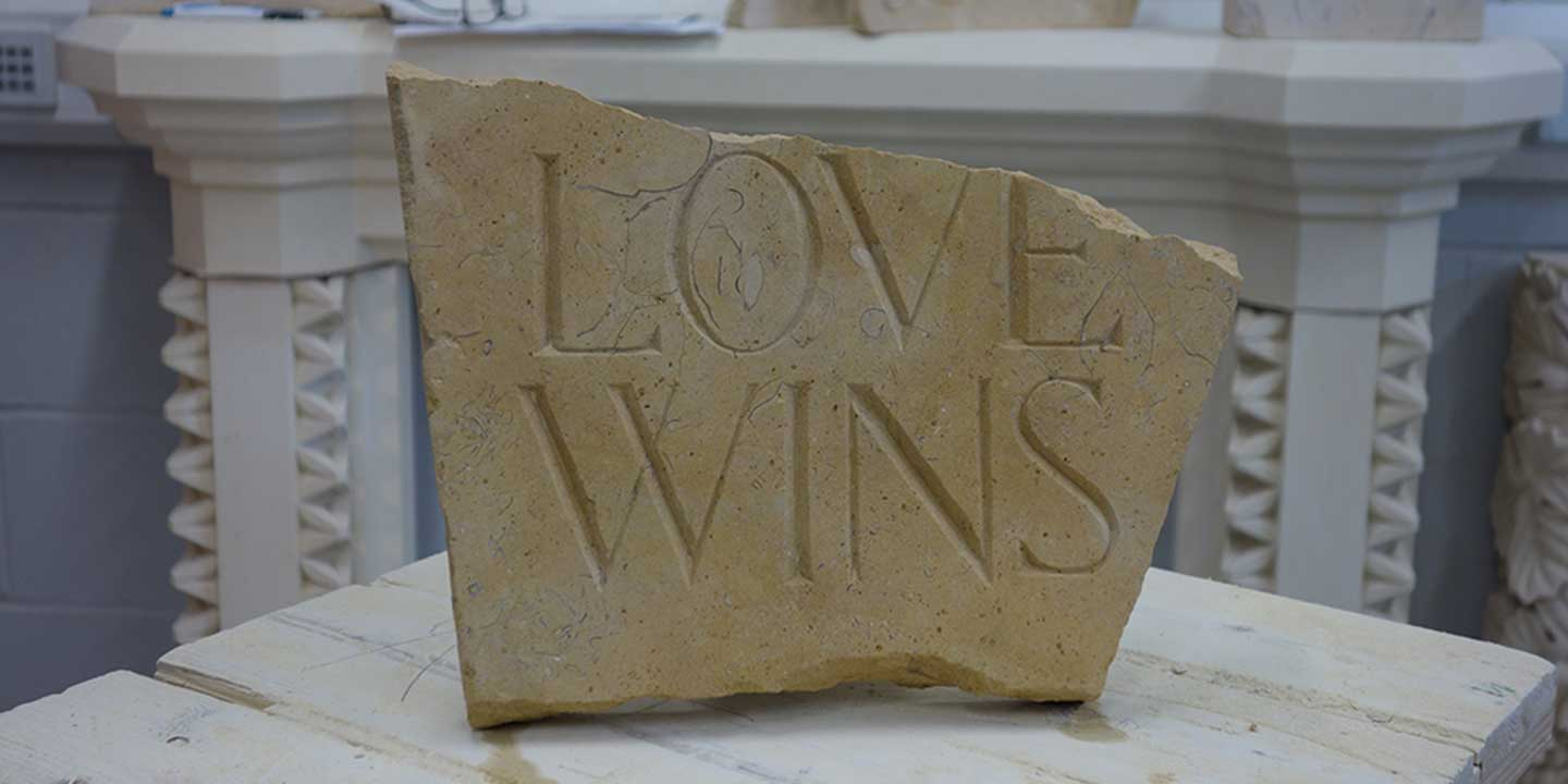 Showcase photo of final class assignment, which is a stone with words LOVE WINS; photo taken inside Ministry of Stone studio, Lincoln, England