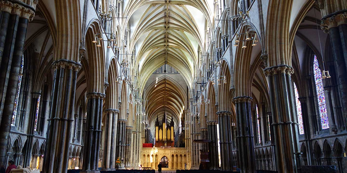 Panoramic interior image of nave of Lincoln Cathedral showing columns and soaring, arched ceiling