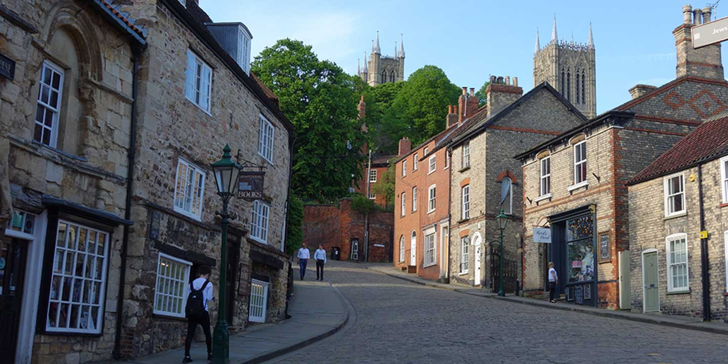 Panoramic image of Steep Hill, Lincoln, England, with cobbled streets, shops and restaurants with spire of Lincoln Cathedral in distance