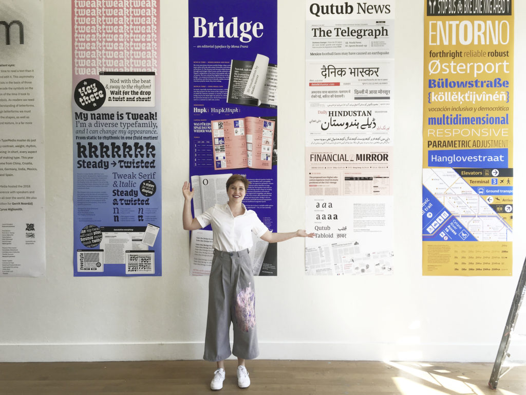 2,60 meter long Bridge poster at the TypeMedia exhibition 2018 surrounded by classmates posters. Mona Franz is standing in front of her poster. 3D elements were made by Studio Meeer.