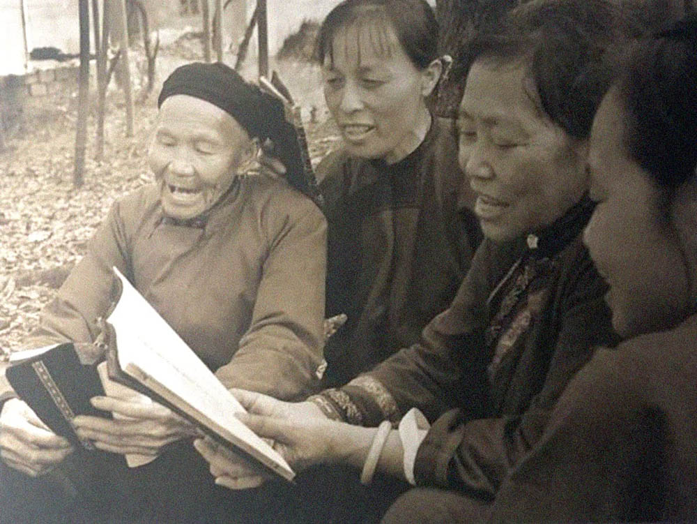 Photograph of four women singing and reading songs around a book written in Nüshu