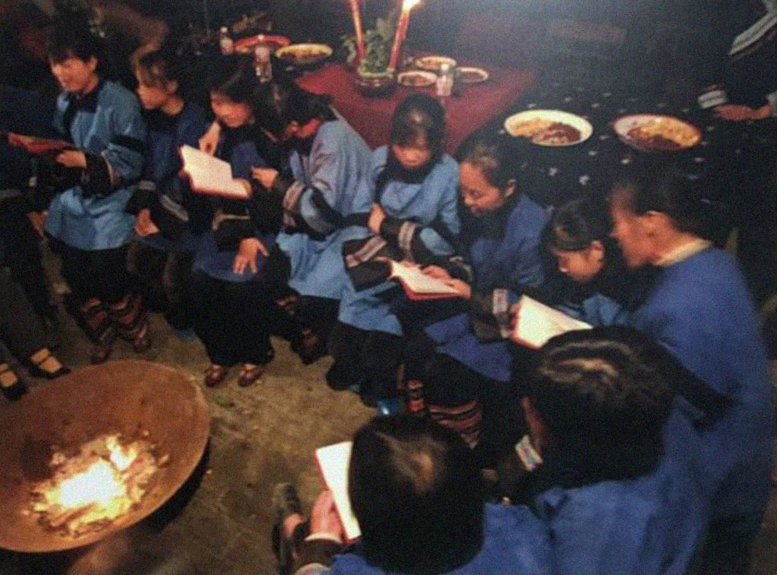 Photograph of women learning Nüshu in a village hall sat around a fire
