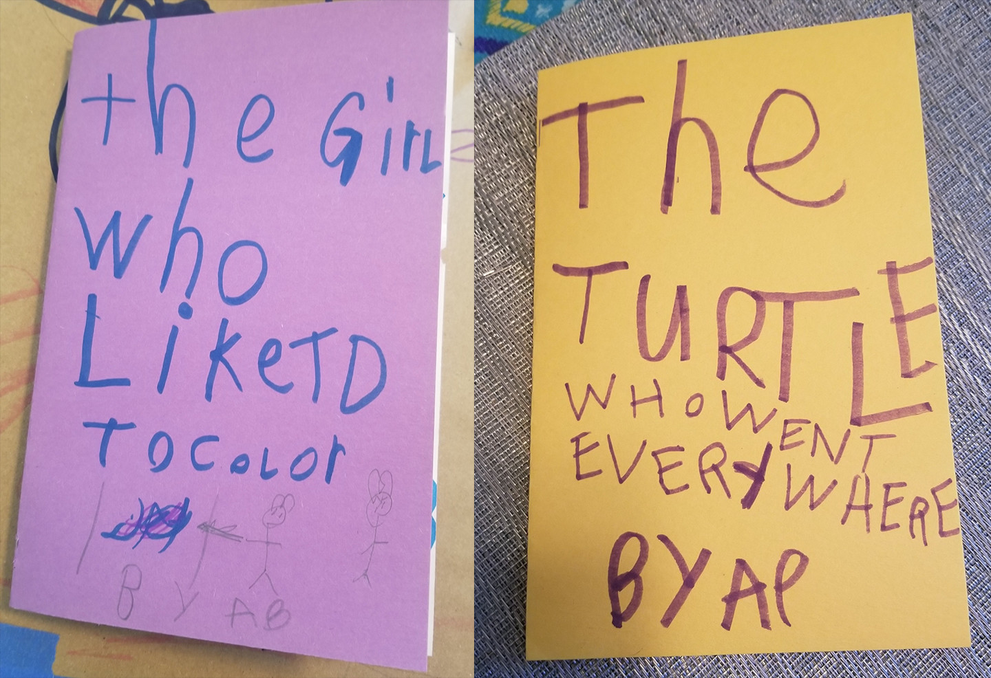 book covers on purple and yellow construction paper, handwritten by a child,