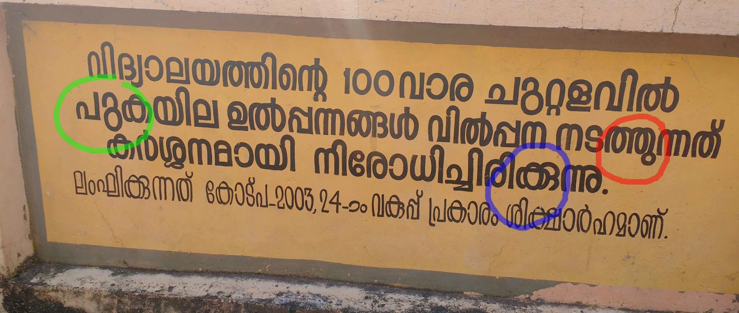 The image of a wall writing in Malayalam. The usage of reformed and traditional orthography with detatched and attached u-signs respectively can be seen. The wrongly used attached u-sign is also shown.